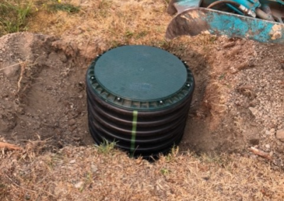 Septic tank lid risers being installed